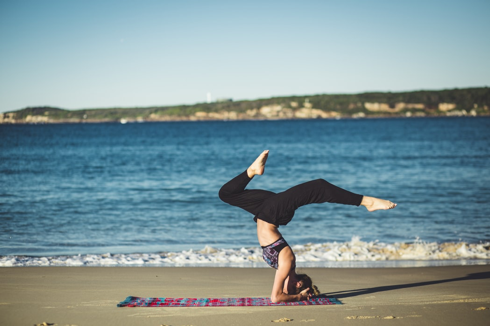 person doing yoga on beach
