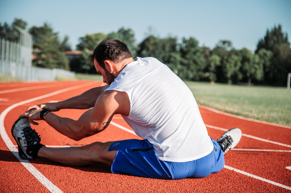 A man stretching on a running track.