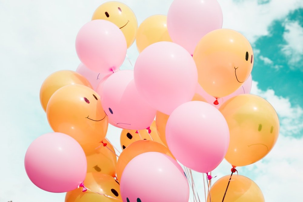 pink and yellow balloons with smiley faces