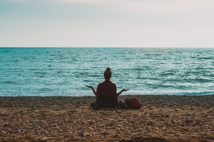 A person relaxing on a beach with the sea