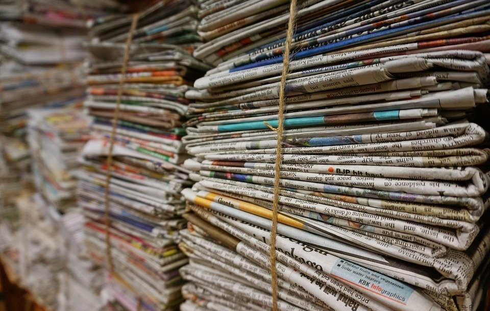 Stacks of newspapers with adverts