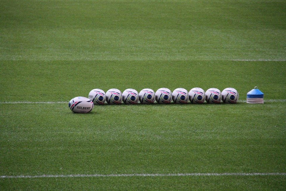 Rugby balls on a training pitch by cones