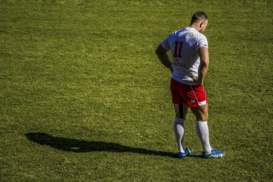 A downcast rugby player alone on a pitch
