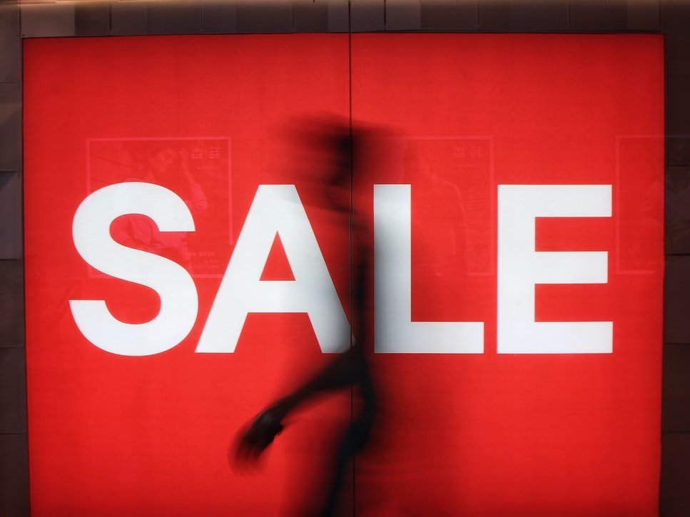 A man walking in front of a red sale sign in a store