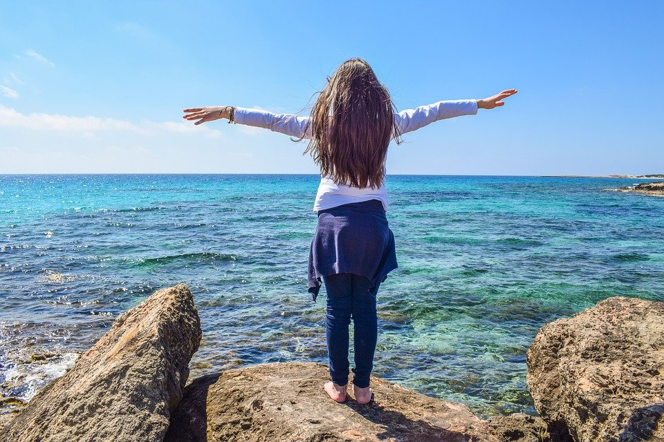 A healthy woman overlooking the sea with her arms stretched out